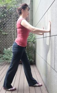 壁の前に立ち、大きく一歩踏み出して壁に両手をつきます