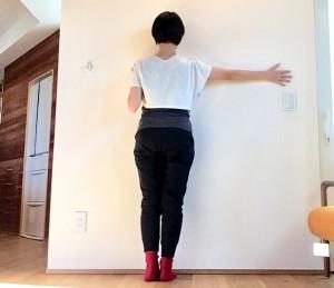 壁に向かって立ちます。足のつま先が壁に当たるところまで近づきましょう。片腕を肩の高さで横にのばし、手のひらを壁につけます