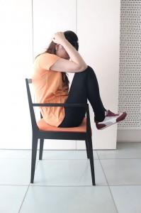 座面に手を添え椅子に浅く腰掛けます。膝とおでこがタッチするように膝をひきよせます。この時、両ひざを離さないようにしましょう。