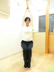 背筋を伸ばし手の平をつけ、頭の上まであげます。この時、足の裏はしっかりと床につけるようにしましょう