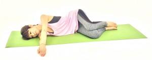 膝を曲げ、床に横になり、両腕を伸ばし手のひらを合わせます