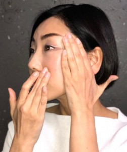 頬を軽く引き上げ、ほうれい線の気になる部分に沿って中指で小さく「らせん」を描いて筋肉をほぐします