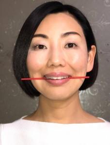 左右の前歯から、口の奥に向かって4本目の歯の後ろでストローを挟みます。ストローが折れないように、頬と口角を上げてキープします