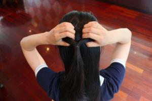 結び目のすぐ上を半分に分けて、結んだ毛束を上から下に通します