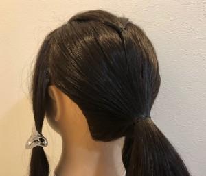 分け目の部分の毛をとり、後ろで結びます。両サイド(耳の上)の毛束を残し、最初に小さく束ねた毛と、残りの毛を一つに結びます