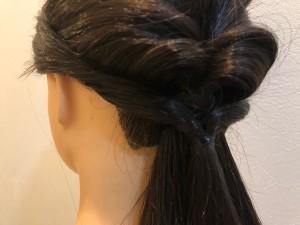 残った両サイドの毛を生え際に沿わせるように後ろでまとめ、最初にくるりんぱをつくったのゴムの上で結び、2つ目のくるりんぱをつくります