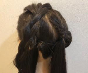 頭頂部の毛束を取り、緩めな三つ編みを1本つくります。残りの毛をさらに斜めに2つに分け、それぞれゴムで結びくるりんぱをつくります
