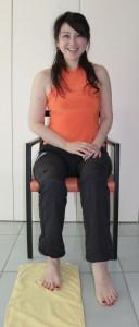 イスに座り、床に広げたタオルの上に片足を乗せます