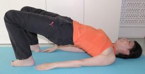 息を吸って、吐きながら骨盤を上にあげます。上半身からヒザまでが一直線になるようし、10秒間キープしておろします