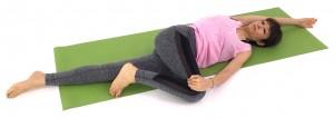 床に仰向けになり右ひざを曲げ、ゆっくり左側に倒しましょう。吐く息とともにひざを床に近づけます