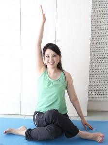 下に置いた足に手を伸ばし、反対の手を上にあげます。この時、肘のポジションが耳の横にくると良いです。できない方はできる範囲で行ってください。頭をまっすぐにキープすることを意識しましょう