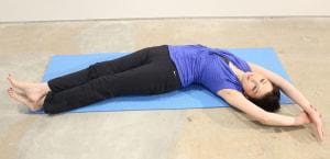 右足を左足の上にクロスさせ、右の手首をつかんで身体を左側にかたむけます。身体でなだらかなカーブをえがき、横側全体を伸ばします。
