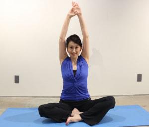 右足を手前にし、足をクロスしてフロアに座ります。左手を上にして手を重ね、両手を頭の上に伸ばしましょう