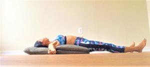 クッションの1つ目のところに頭、2つ目に胸がくるくらいの位置に仰向けになります。両腕を横に開き、手のひらは上向きにします。足はリラックスしやすい幅に少し開いておきましょう