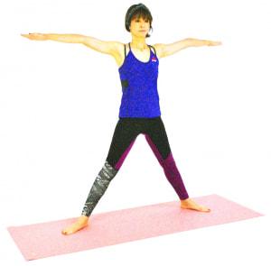 足を大きく開き、両腕を肩の高さに伸ばします。つま先は斜めに向けて軽くあごを引き、背骨を伸ばしましょう。吐く息とともにお腹を腰に引き寄せドローイング(吐く息とともにお腹を腰に引き寄せる)します