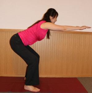 足を腰幅に開いて背筋を伸ばし、胸を張ります。腰を後ろに引きながらゆっくり落とします。この時、腕は床と平行になるようにまっすぐ伸ばしましょう
