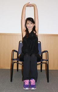 椅子に座って、両手を合わせて手を伸ばします