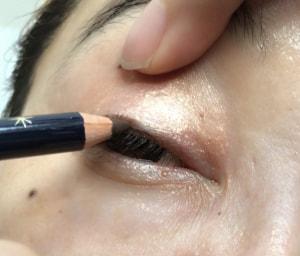 まつ毛の間を埋めるように引くには、片手でまぶたを引き上げ、ペンシルを左右に動かしながら描きます。目は、少しだけ開いた状態で描くと描きやすいですよ
