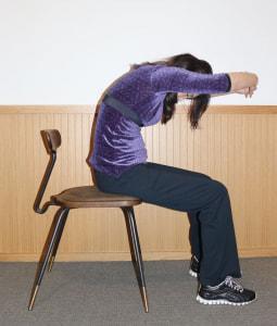 腕を前で組んでおへそを覗き込み、10秒キープします。左右の肩甲骨を開いて、可動域を広げます