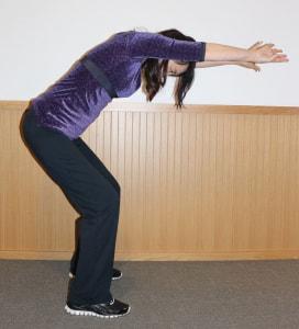 足を腰幅に開いてひざを軽く曲げ、手の甲を合わせるように腕を床と平行に伸ばします。おへそを覗き込むようにして、身体を丸めます。この時、できるだけ骨盤を後ろに倒して背骨を丸めましょう