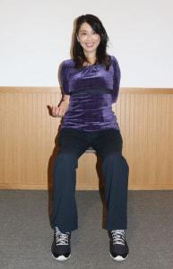 足を腰幅に開いてイスに座り、身体の横で右ひじを曲げます。左手を背中側から右ひじにそえ、肩を開きます。この時、頭をかたむけず、まっすぐにキープしてください