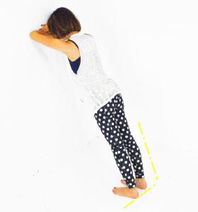 壁に両肘をつけて、重ねた腕の上に額をつけます。そこからかかとが床につく(押せる)位置を見つけてください。