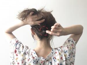 両方のサイドをねじったら、後ろでクロスさせます。クロスした毛の毛先を、一つ結びの下で結びます