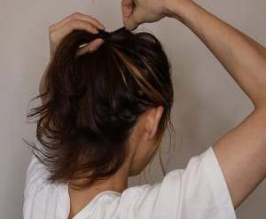 頭のシルエットをきれいに見せてラフ感をアップするために、親指と人差し指の爪を使って一つ結びにした表面の毛束を引き出していきます