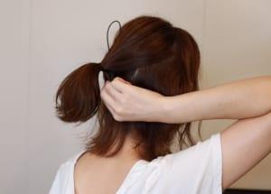 裏側から100均で買った道具を通し、髪の毛の表面に道具の先端部分(穴が空いている部分)が出るようにします。この時、まっすぐ通すのではなく、少し斜めに通すことがポイントです