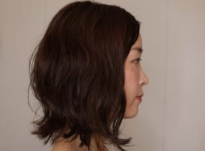 表面をストレートにしたい時は、手グシでストレートにしながらスタイリング剤をつければOKですが、今回はあえて、パーマ風のウェーブ感を出すために、髪の毛の表面も揉み込むようにスタイリング剤をつけています
