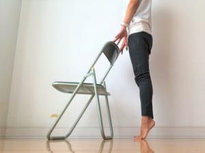 バランスを崩さないようにイスの背もたれやテーブル、壁に手をかけます。かかとを上げて、「つま先立ち」になります