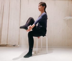 イスに座った状態で片足を持ち上げ、かかとの内側やスネの内側をタッチします。この時、上げている足と同じ方のお尻へ、しっかりと体重を乗せてください。骨盤を少し後ろに倒してもOKです