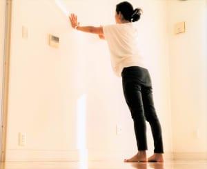 足を腰幅より少し大きめにひらき、壁の前に立ちます。両腕を伸ばし、肩幅くらいにひらいて壁につきます。この時、肩と同じくらいの高さ、もしくは肩より少し上の位置に両手をつけましょう