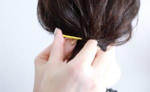 毛先をピンに巻きつけたら、ピンを閉じた状態のままゴム付近に差し込みます