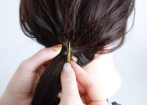 ピンを閉じた状態で端が短い部分を下にし、ゴムに巻き付けた毛束の表面と毛先を合わせてピンですくいます。地肌に対してピンが垂直になるように押し込んでいきます