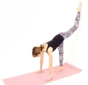 壁から20cmほどはなれ、背を向けて立ちます。右ひざを曲げて両手を床につけます。左足の甲を壁にそえます。ひざをロックしないように、軽く曲げた状態を維持してください