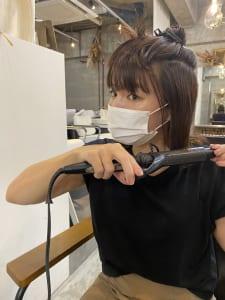 こめかみから下の髪を外ハネに巻きます。ポイントは、巻きすぎないことです。コテに、外ハネにする部分の髪を巻きつけ、1カールつけないくらいで形をつけます