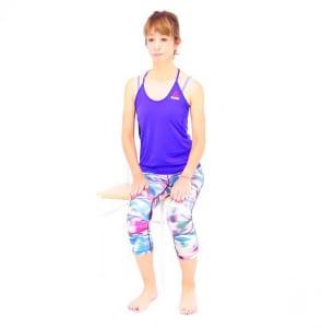 イスに腰かけます。曲げる脚を動作しやすいように、横にずらし、お尻も横にずらします(この場合、左のお尻をイスから横にずらす)
