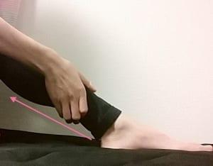 足首を横からつかみます。中指の腹を使って足首裏の付け根からふくらはぎをまっすぐ通り、ひざ裏の真ん中にあるツボ(委中)をプッシュします。5回ほど行いましょう