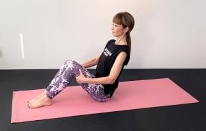 床に体育座りのように座り、両手のひらを膝裏にそえます。吐く息とともにドローイングしながら、腰骨→肩→耳のラインを一直線にしましょう。この時、胸を引き上げ、肩甲骨を下げて姿勢を整えます