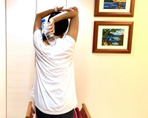 床やイスに背筋を伸ばして座ります。ペットボトルを持っている側の肘を身体の後ろ側で曲げ、反対側の手で肘の位置が動かないように固定&サポートします