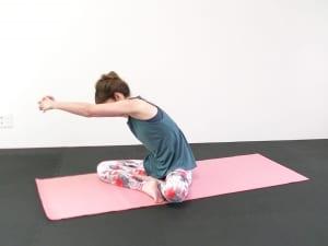 座り姿勢から両指先をからめ、手の甲を前に押し出します。腕の力をゆるめて、肩甲骨を左右にゆらしながら背中や腰のこわばりをとります