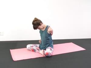 そのまま両腕を右腰にそえます。大きく息を吸いながら顔を正面に向けて吐く息で頭を右側に倒し、左首筋を伸ばしましょう。目線を斜め左下にさげて、ゆっくり頭を回します