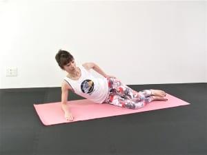 右の腰を下にして床に横寝になり、両膝を直角に曲げて重ねます。右の肩の真下に肘をそえて、おへそを正面に向けます。鍛えている筋肉に意識を向けるために、左手をお尻にそえます