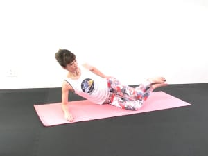 さらに、かかとを床からはなします。おへそを正面に、肘で床を押して右わき腹が床に落ちないように注意してください。右肩も耳と近づかないように、肩を下げる意識も忘れないでくださいね