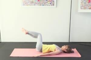)一度息を吸って、吐く息で両膝を右方向に傾けます。この時、両方の肩甲骨が床からはなれない位置まで傾けてください。吸う息で両膝を正面に戻し、吐く息で左方向に傾けます