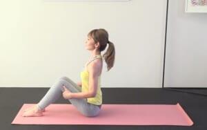 体育座りのように、膝を立てて床に座ります。足幅を握りこぶしひとつくらい開き、両手で太ももをつかみます。お腹と腰を引き寄せ、恥骨とおへそを遠くはなすようにして重力に負けない美しい姿勢を作ります