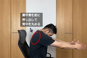 腕を前に押し出して背中を丸めます。肩甲骨を前に押し出すようなイメージです。腕を前に押し出す時は、息は吐きながら行ってください