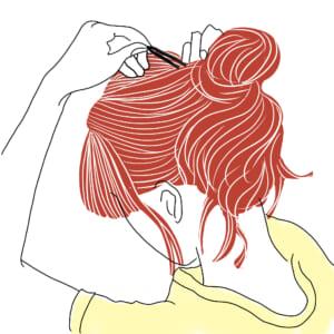 (1)で残した毛先をゴムで結んだ部分に巻きつけてゴムを隠し、お団子の両端をピンで2カ所留めます