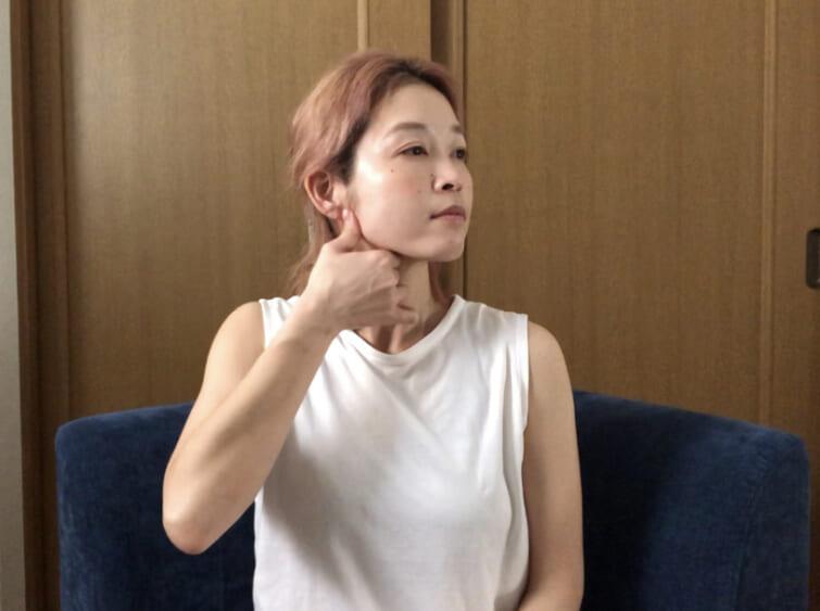 親指でエラを4回なぞります。エラ周りはむくんでいる方ほど痛みやこりを感じやすいので、少し長めにマッサージしてもよいでしょう。4回マッサージしたら、首に手をあてて鎖骨に向かって2回スライドさせます